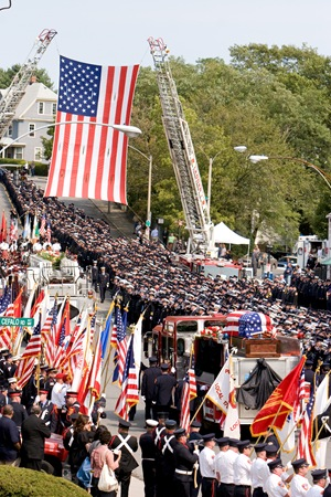 Thousands of firefighters from around the country line the street as fire engine bearing the casket of Paul Cahill is carried away from Holy Name Church in West Roxbury, Mass. Cardinal Sean P. O'Malley presided at the Sept. 6 funeral Mass for the fallen Boston firefighter.  Pilot photo/ Gregory L. Tracy