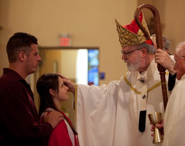 Cardinal Seán confirms the confirmation class at St. George Church in Framingham this past Sunday. Photo by George Martell