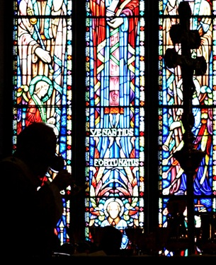 Archbishop O'Malley is silhouetted against the stained glass windows of the Cathedral as he celebrates the Eucharist.  Pilot photo by Gregory L. Tracy