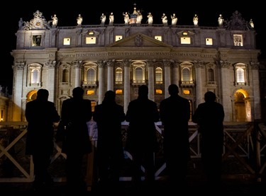 Six men pray the rosary in Spanish in front of St. Peter's Basilica Feb. 28, minutes after the period of Sede Vacante began.  Pilot photo/Gregory L.  Tracy