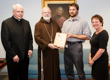 """Pilot staff reporter Christopher S. Pineo receives his plaque of the Pontifical Mission Societies' Archbishop Edward T. O'Meara Award from Cardinal Seán P. O'Malley Aug. 13, 2014. Pineo took first place in the category of Mission Animation News for his Aug. 30, 2013 story """"Plymouth Religious Ed Students Use Lemonade Stand to Spread the Good News."""" First presented in 1993, the award recognizes excellence in coverage of world mission news in the Catholic press.<br /> Pilot photo/ Gregory L. Tracy<br />"""