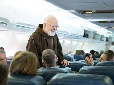Cardinal O'Malley greets passengers aboard the plane heading to Havana to attend the Mass celebrated by Pope Francis Sept. 20. Pilot photo/ Gregory L. Tracy